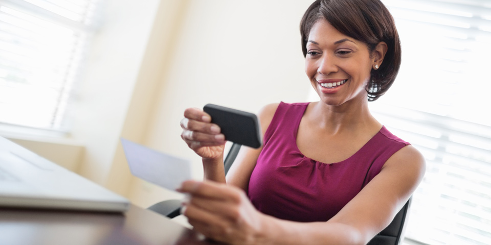 Business woman holding paper check using smart phone
